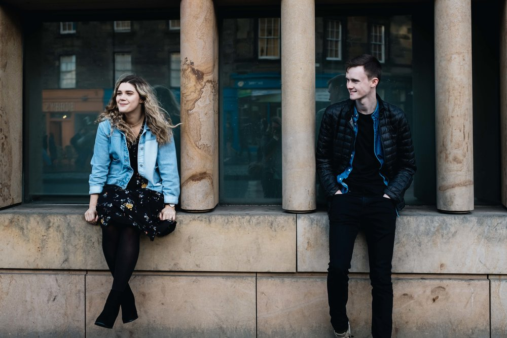 a smiling engaged couple sitting on a wall looking away from the camera