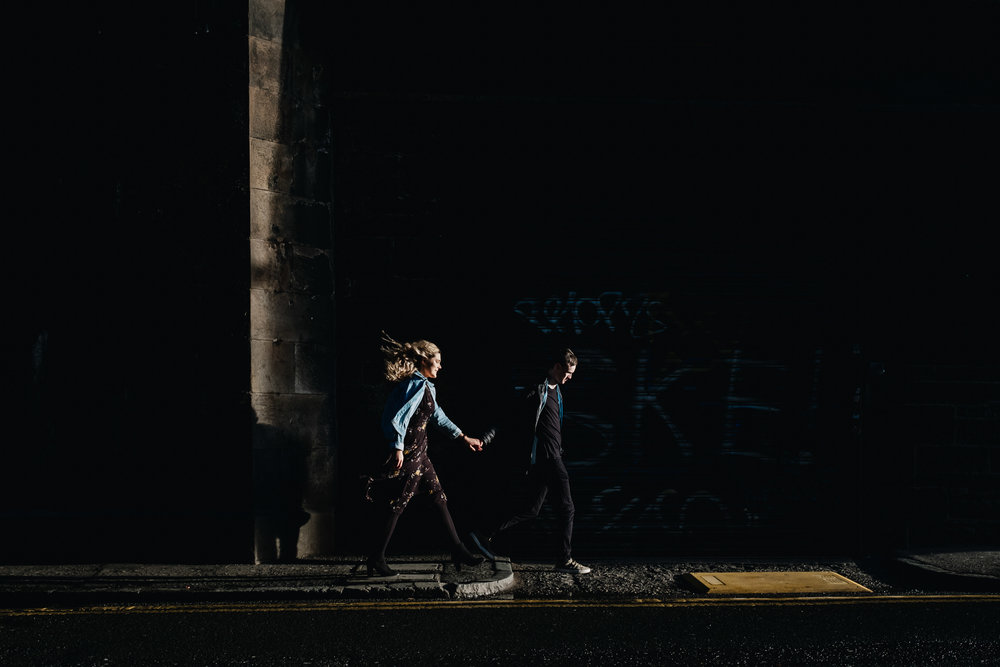 An engaged couple are walking along a street but the only part visible of them is their heads as the scene is in shadow
