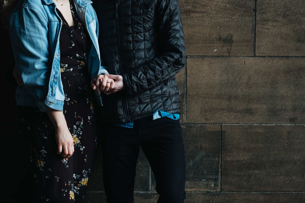An engaged couple lean against a wall at Edinburgh University holding hands.