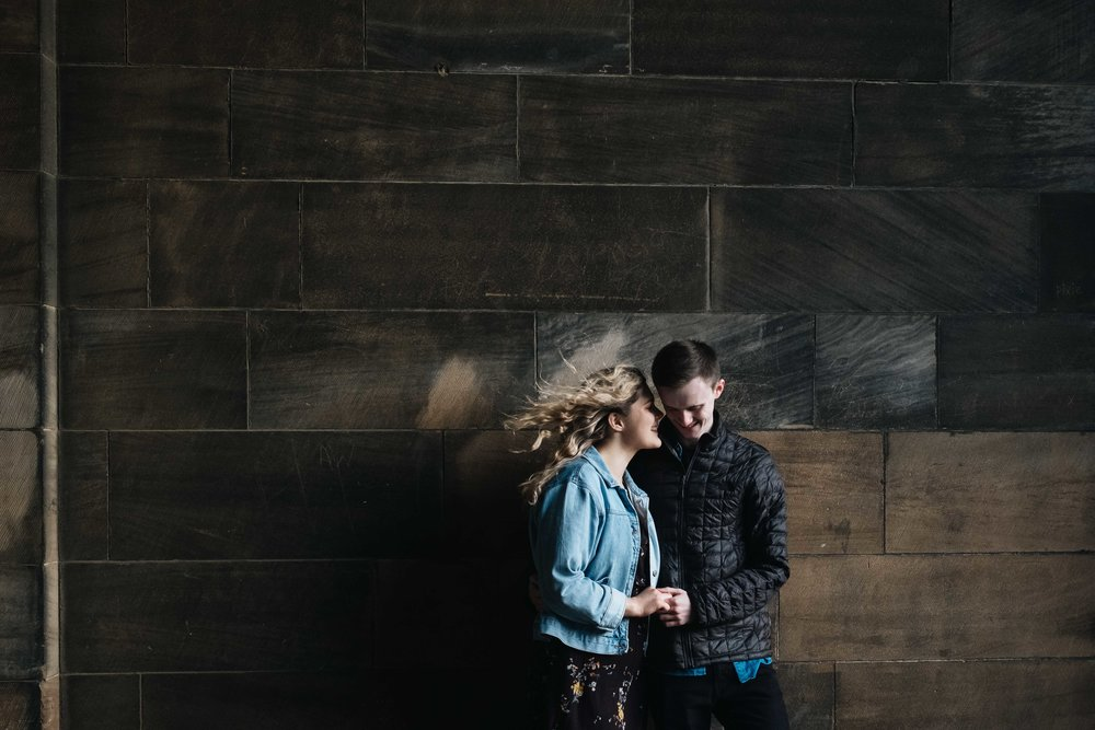An engaged couple lean against a wall at Edinburgh University holding hands. Her hair is blowing in the wind