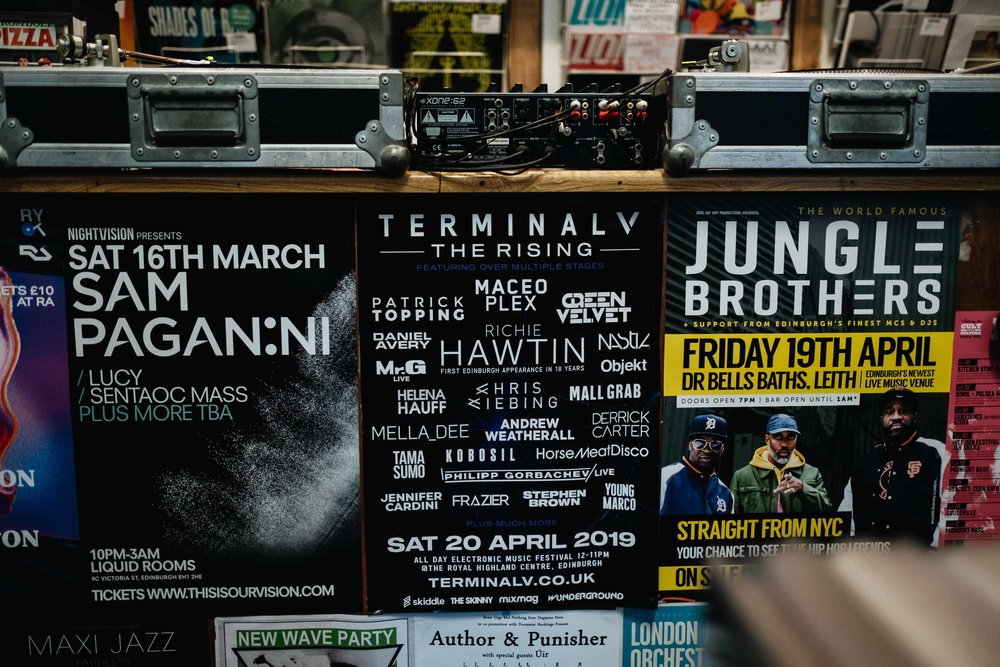 Posters advertising forthcoming music events in a record store.