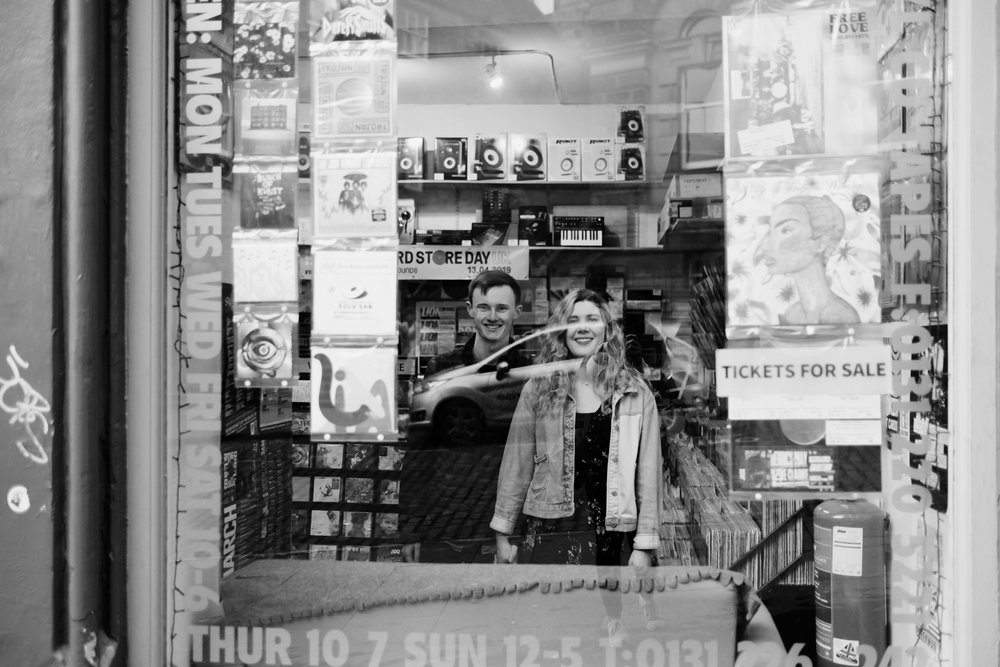 A couple stand looking out of the window of a record store, smiling.