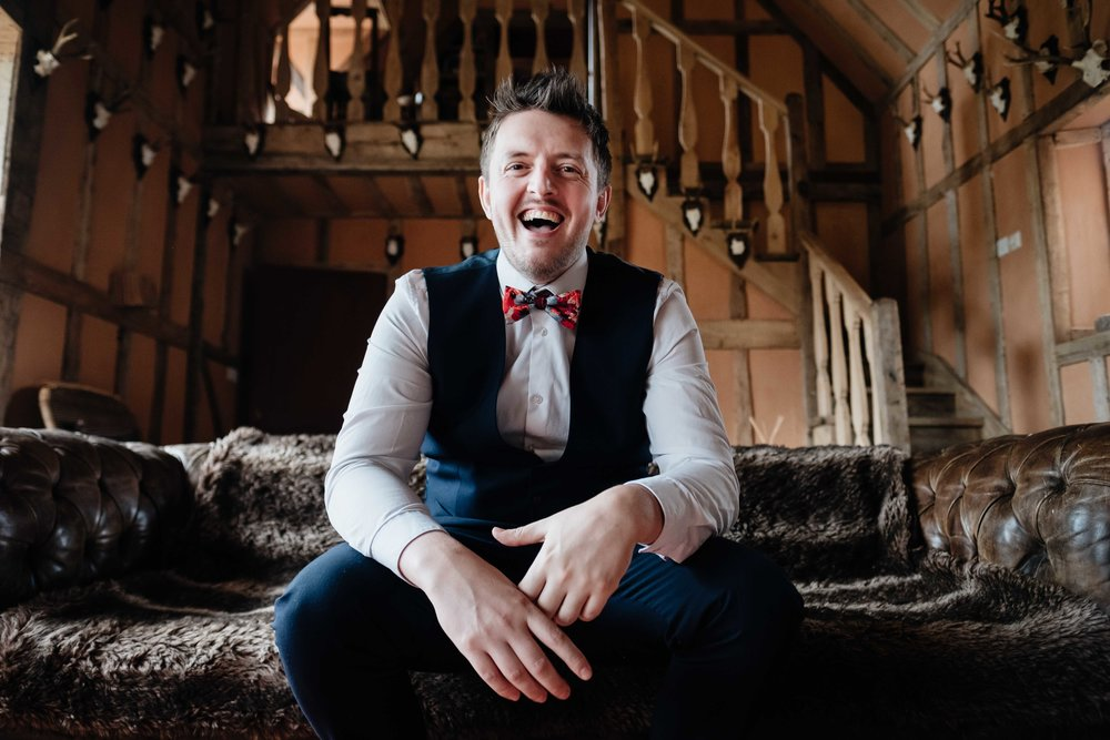 A groom with a suit and bow tie sits laughing on a sofa