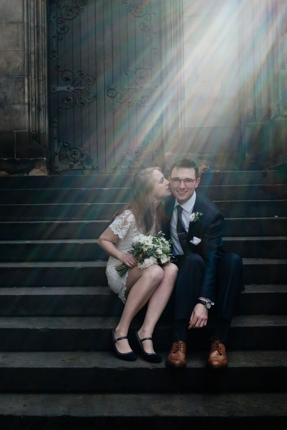 A couple are sitting on the steps of St Giles in Edinburgh their elopement