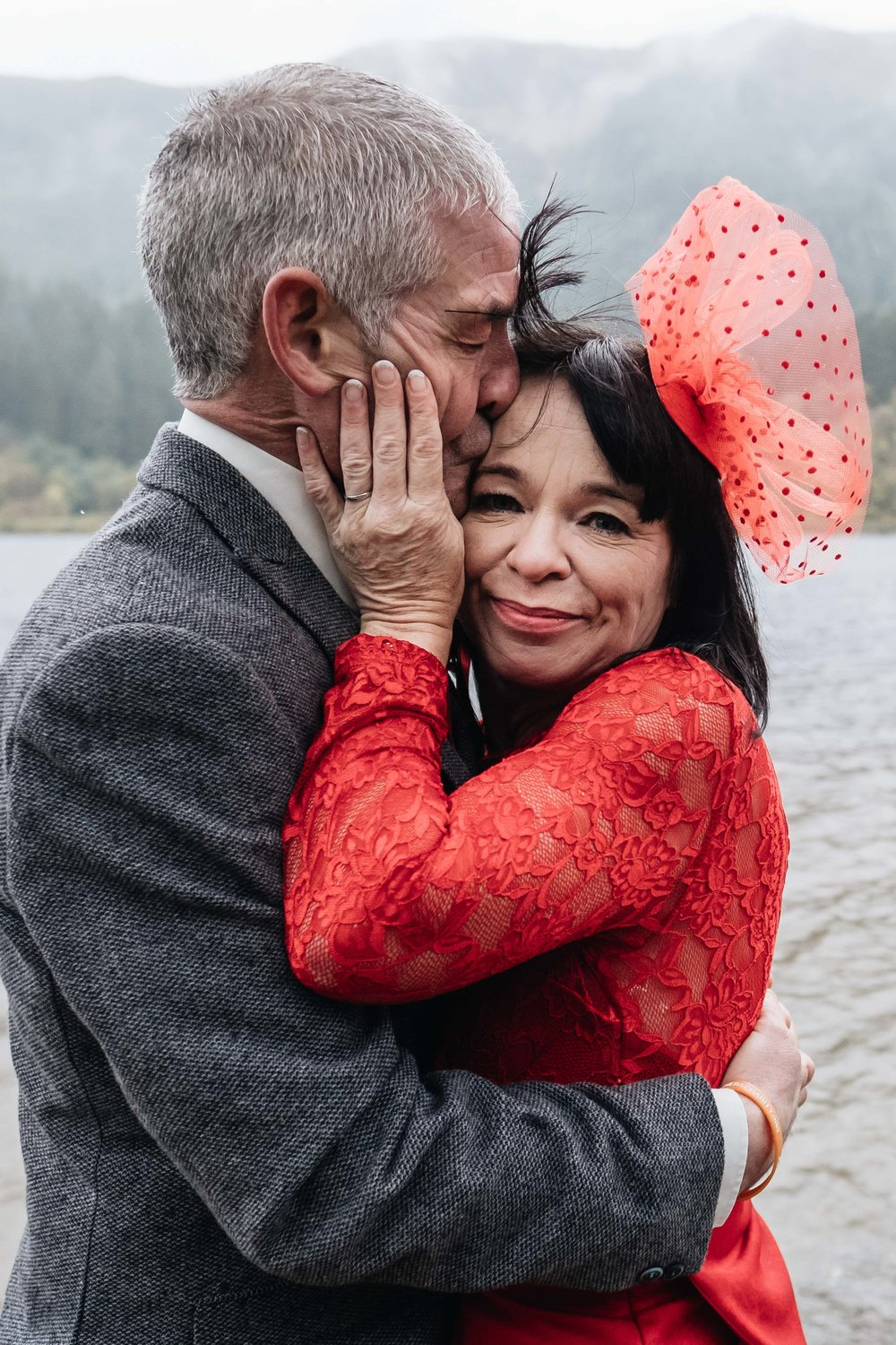 A bride wearing a red dress is hugging her husband.