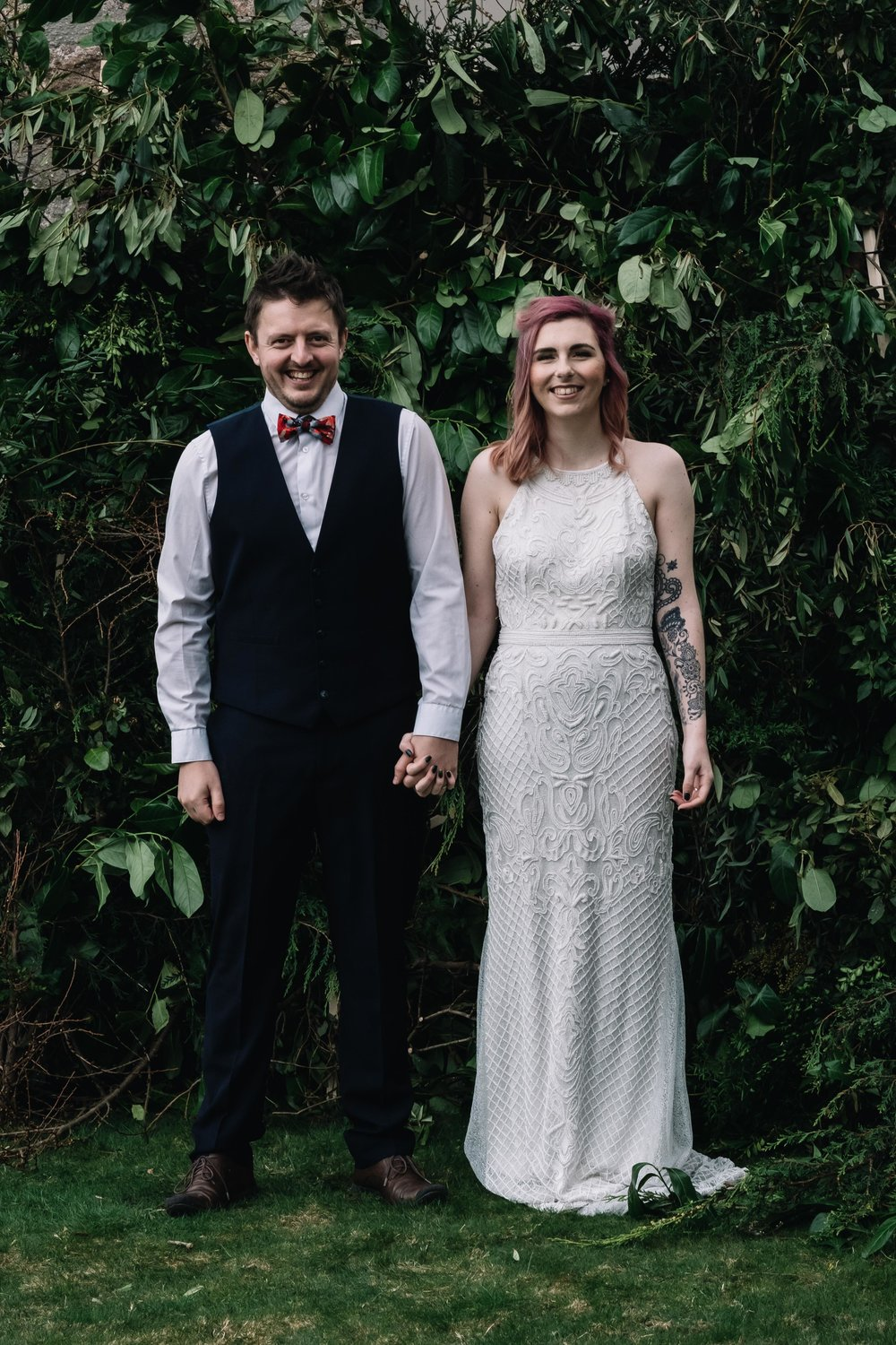 Bride and groom looking to camera holding hands with a green living wall behing them.
