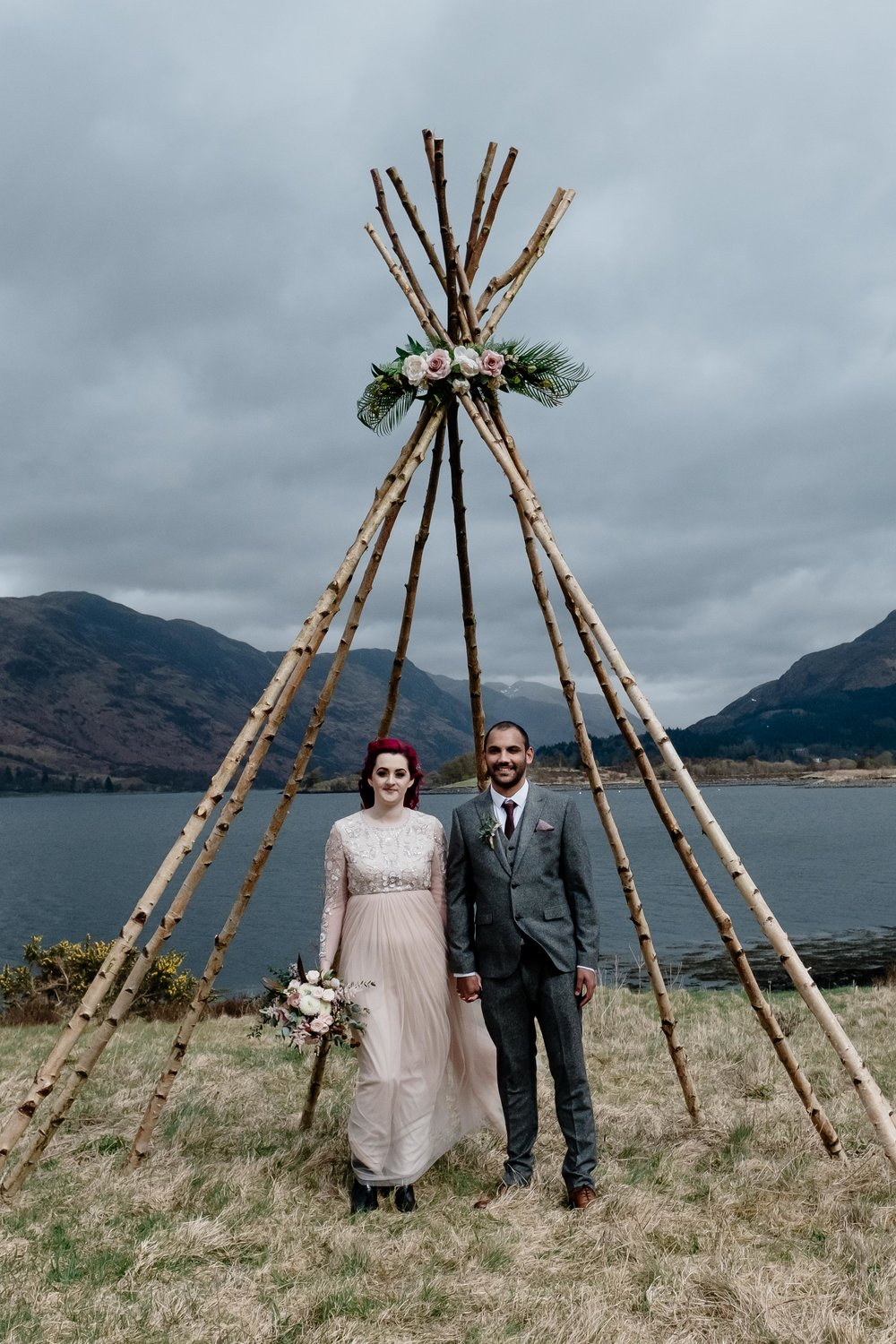 A bride and groom are standing under their teepee in Glencoe