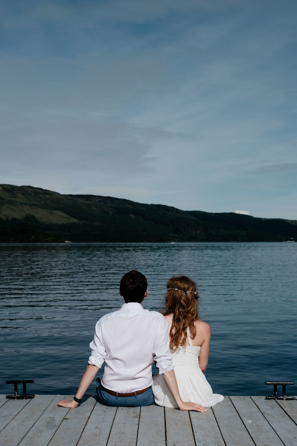 A bride and groom are sitting at the end of a pier.
