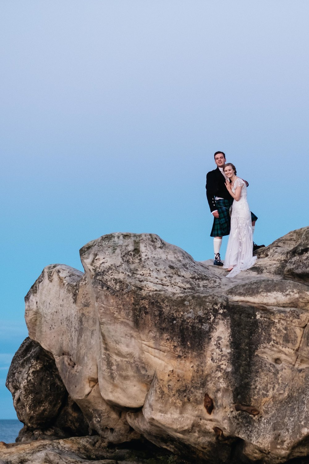 A bride and groom are standing on a rock.