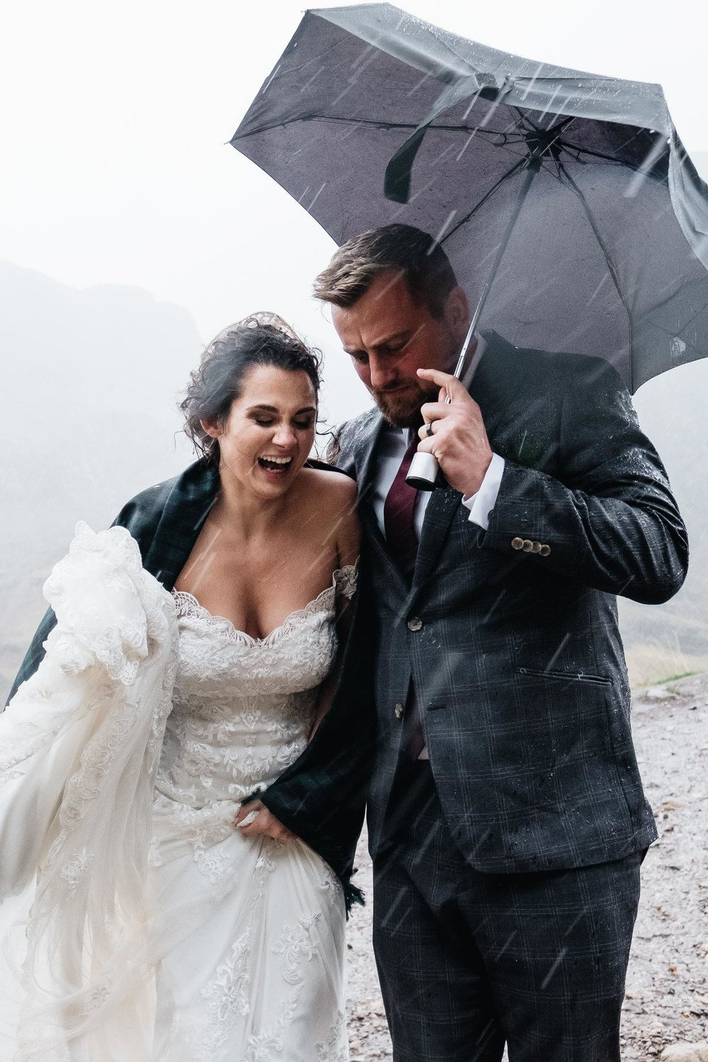 A bride and groom are walking in torrential rain during Glencoe elopement.