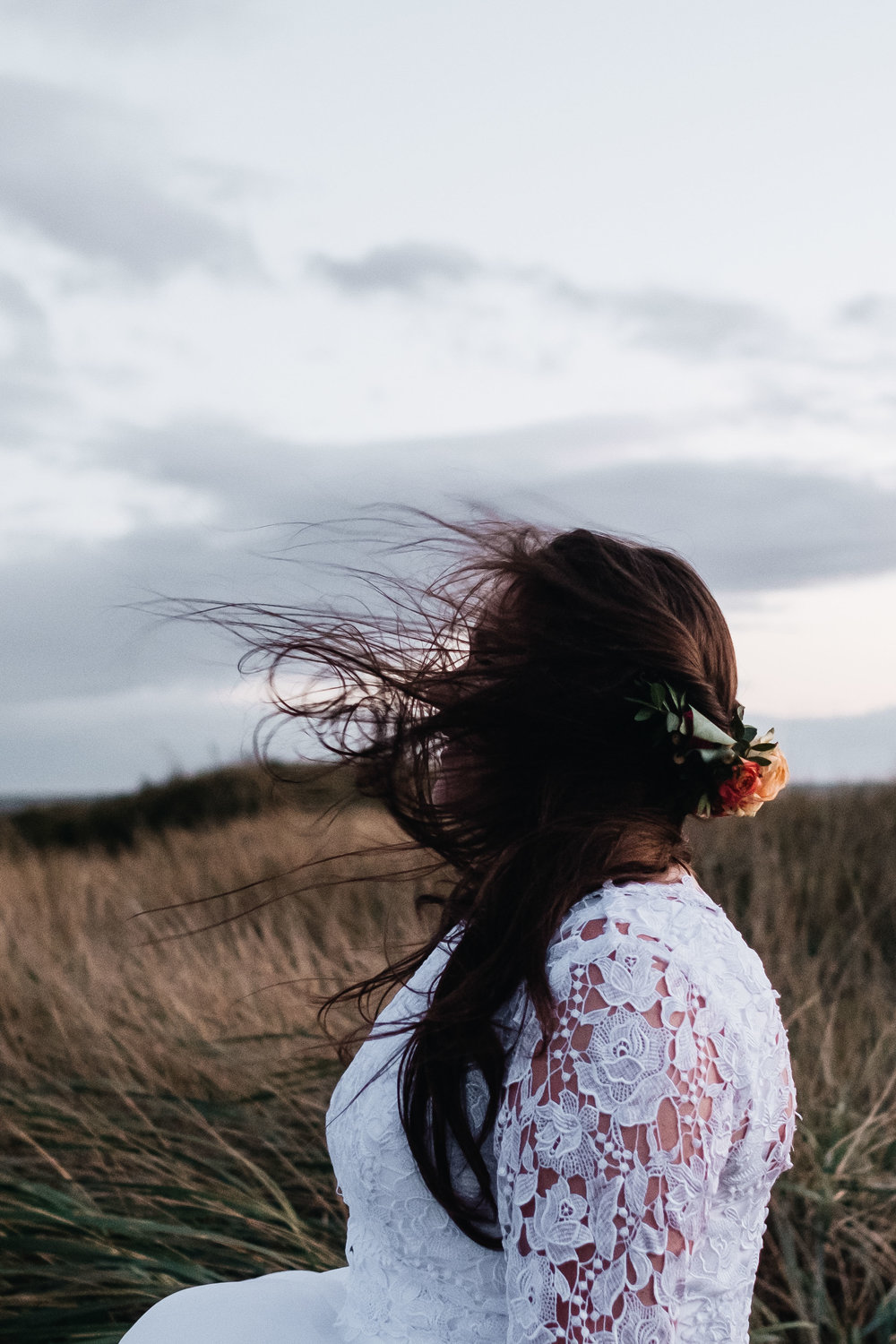 A bride's hair is being blown in the wind.