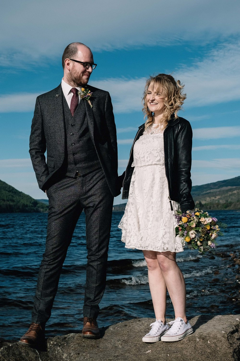 Couple who've eloped are standing on a rock. The bride is wearing a black leather jacket.