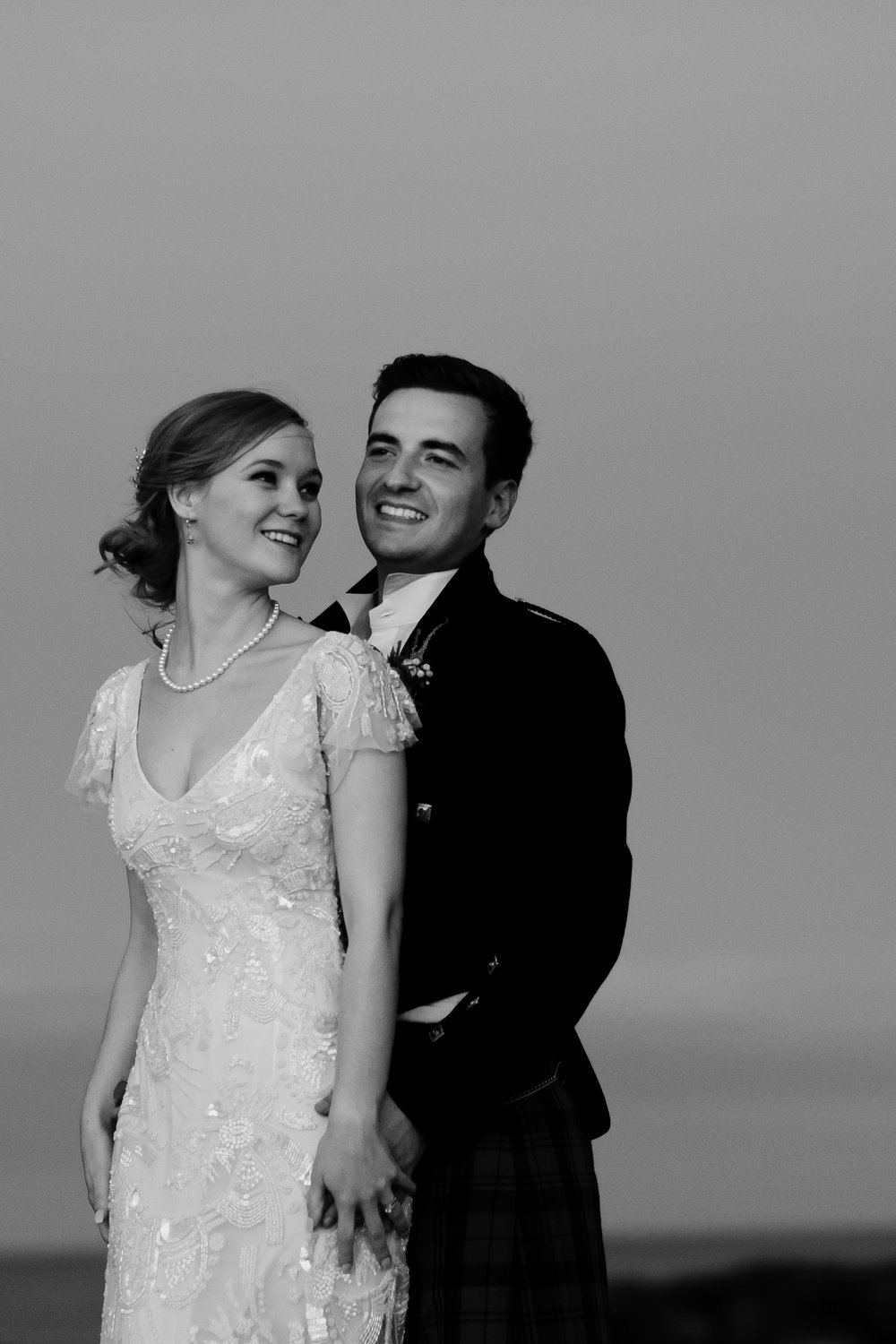 An elegant bride is smiling at her husband who is hugging her.