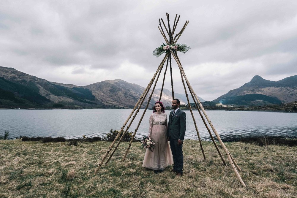 A bride and groom are standing underneath their teepee after their elopement in Glencoe