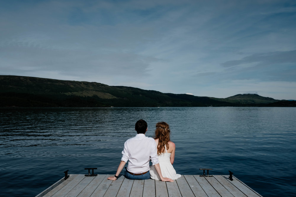 A bride and groom sit with their backs to the camera at the edge of the pier looking out to the loch.