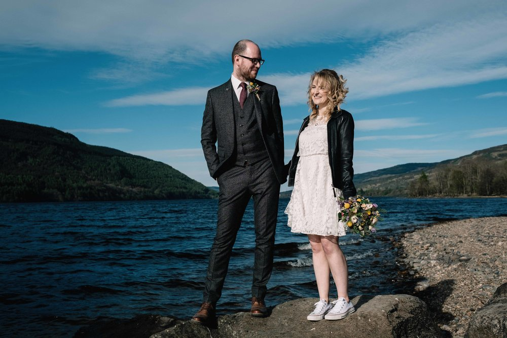 A bride and groom stand on a rock during their lochside elopement