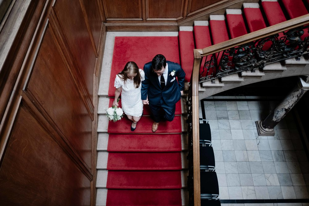 A bride and groom walking down the stairs of the Edinburgh Registry Office following their elopement