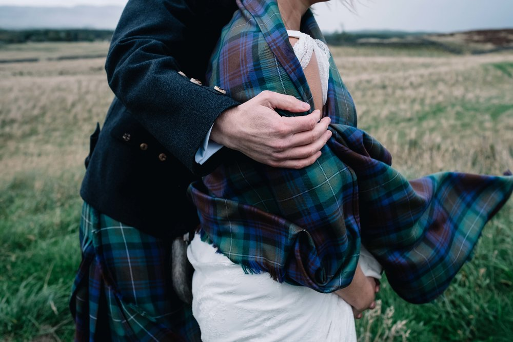 A bride and groom stand in the wind and the groom holds the bride's tartan shawl from blowing in the wind.