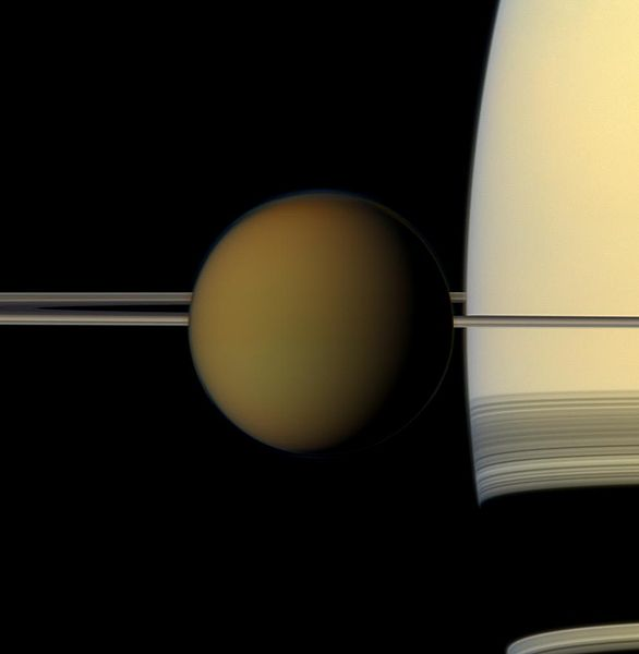 Saturn looms large behind Titan.  (Image credit: NASA)