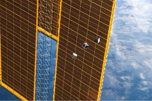CubeSats float past the solar panel of the International Space Station. (Image credit: NASA)