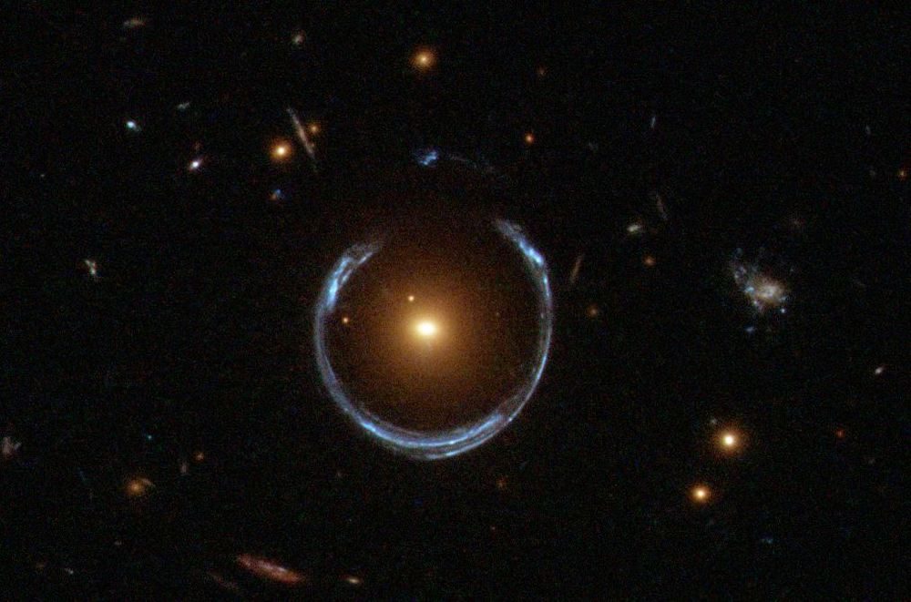 The large red galaxy in this image is acting as a gravitational lens.  Light from a more distant blue galaxy is being lensed by the red galaxy's gravity and bent into the blue arcs seen here (Image credit: ESA/Hubble; NASA).