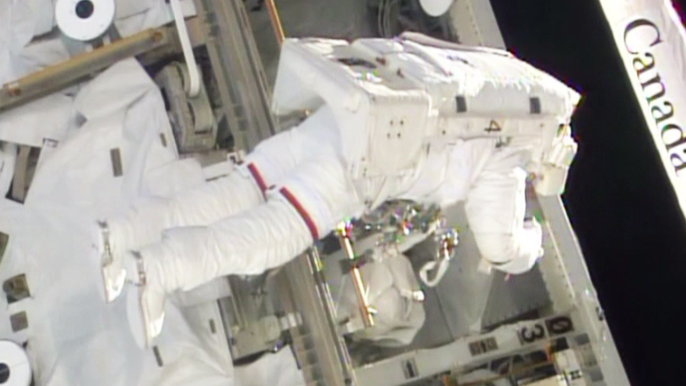 A NASA astronaut replaces a broken computer during today's remarkably-short spacewalk.  (Image credit: NASA)