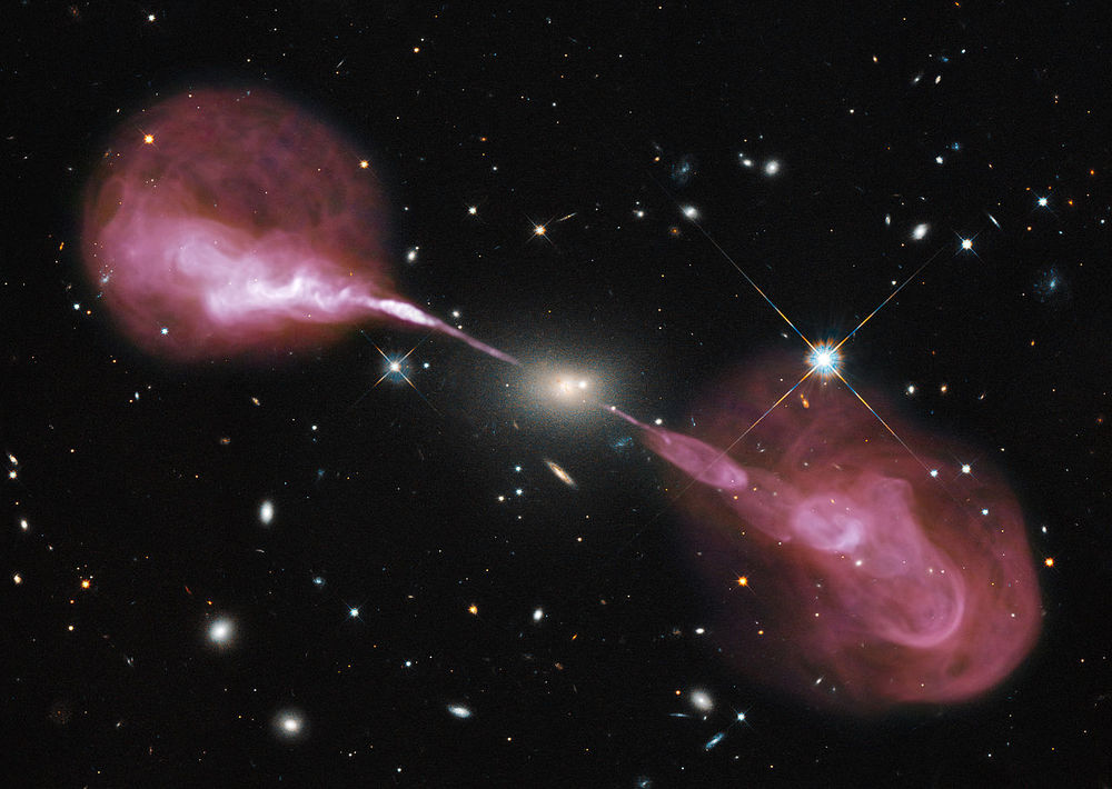 The galaxy Hercules A hosts a powerful supermassive black hole (4 billion times more massive than the sun) that ejects jets of material that astronomers observe at radio frequencies in pink. (Image Credit: NASA, Wikipedia Creative Commons)