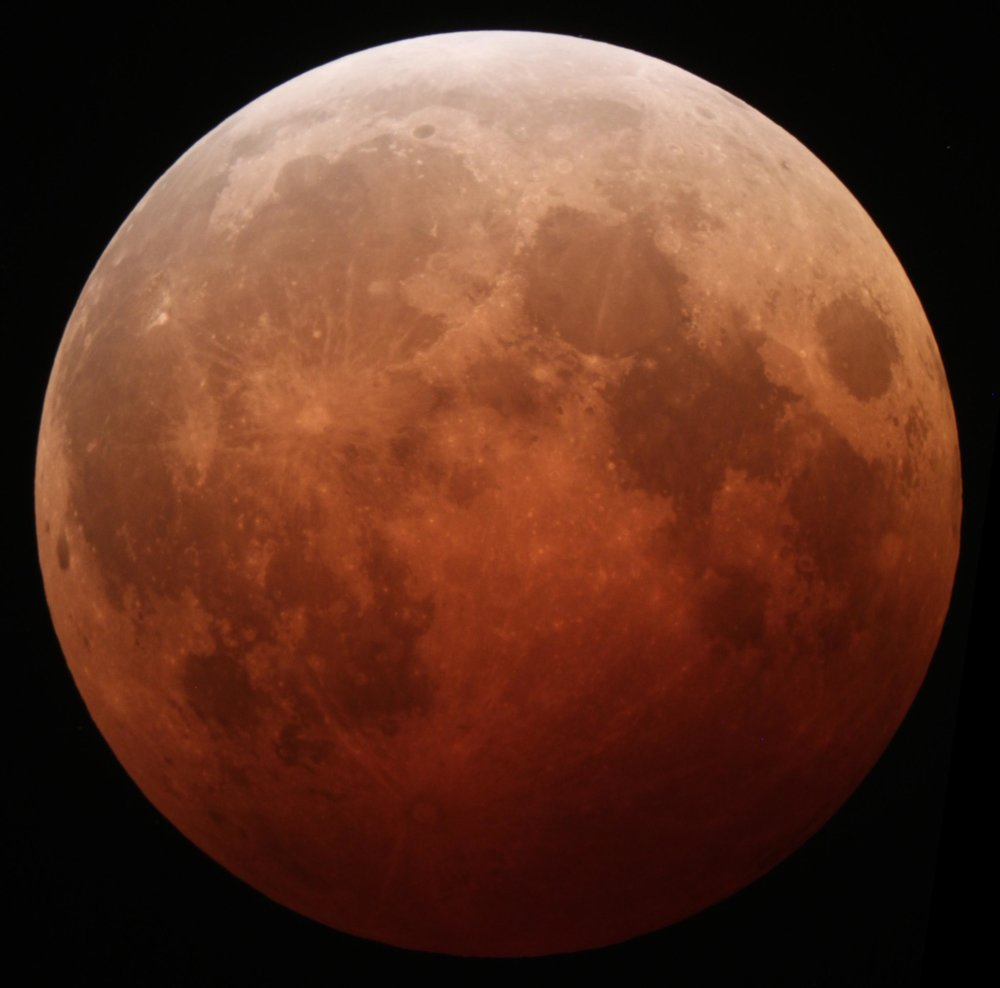 The moon during a lunar eclipse often appears red due to refraction from light bending through Earth's atmosphere. Blue light is higher energy, so it tends to be scattered away by particles in our atmosphere. Hence, only the red light survives to reflect off the lunar surface.  (Image Credit: Alfredo Garcia, Jr., Flickr)