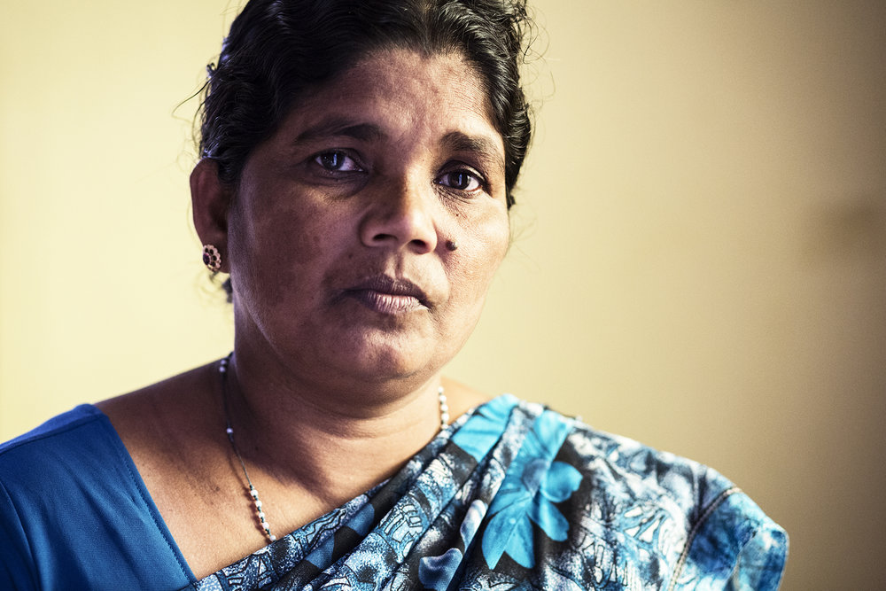 "Immaculata, 47. Immaculata's oldest son was killed in the war in 2006. A year later, the army came to her home and took her younger son upon suspicion that he was involved in the LTTE. He spent several years imprisoned until he falsely confessed in 2014 in order to be released. Since his release from prison, she has been caring for him.  ""He's home with me but he's very ill. He can't sit or sleep properly and he's got psychological problems. He's afraid someone might come and take him to prison again. He's just scared."""