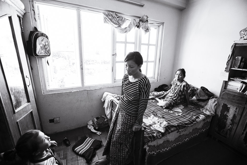Anu stands in the room she shares with her mother, two sisters and one brother.   Anu's father left the family prior to the earthquake. Anu has spent the following months seeking a job to support the family and keep up with rent for the apartment.