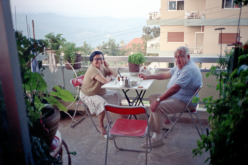 #08 - Earlier that morning and on the same roll of film, Tante Loulou and Ammo Robert (ammo = uncle) on their balcony in Baabdat for their daily morning breakfast ritual consisting of turkish coffee and pills, before heading back to Antelias to their very humble pied-a-terre at the Golden Beach Hotel, where he drops her off and goes to his hardware store, which he's owned since the 1960's, in the same district to work all day. Note the baby blue Izod shirt which will help identify other rolls of the same day, as he had a massive collection of polo type shirts which he cycled through.