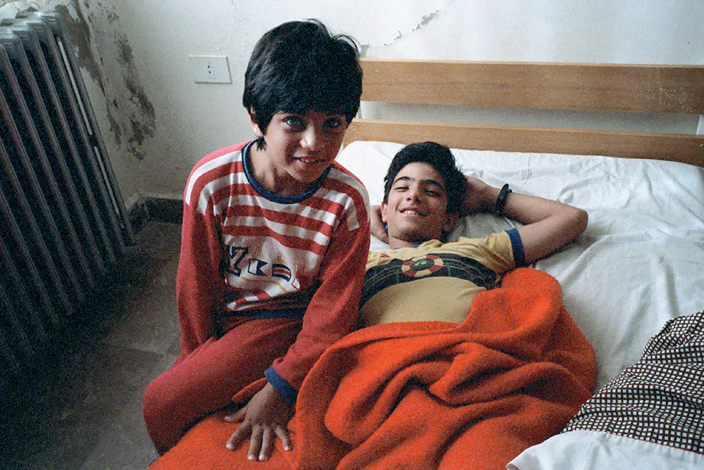 #19 - Karim in the red and white striped pajamas with Jamil in their bedroom in Ashqout.