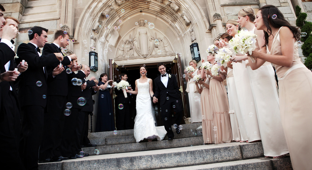 The bride and groom exit the church as the wedding guests blow bubbles during the recessional at Saint Ignatius Church