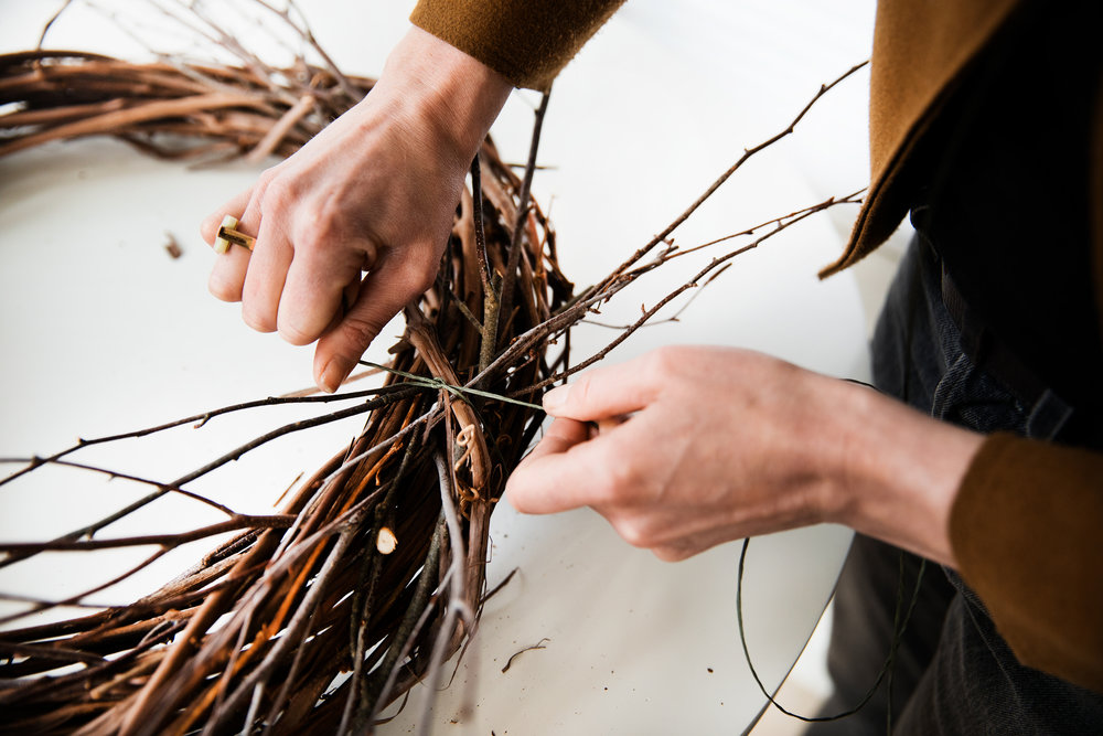Step Two - Use the bind wire to tie the branches taught around the grapevine in any areas where it feels needed. The wire will be covered up with the other floral elements, so no need to worry about it showing at this point.