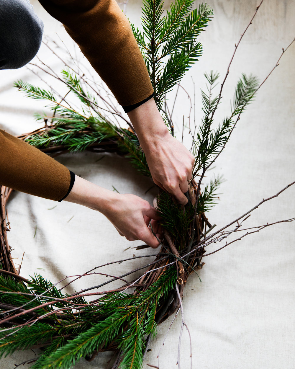 Step Three - Begin adding your evergreen pieces. Intertwine them between the branches and the grapevine wreath, until they are well situated and don't feel loose. You'll want to take some time here to really tuck them into place. Mixing sizes will create a more layered look, so try various arrangements of short pieces alongside long ones.