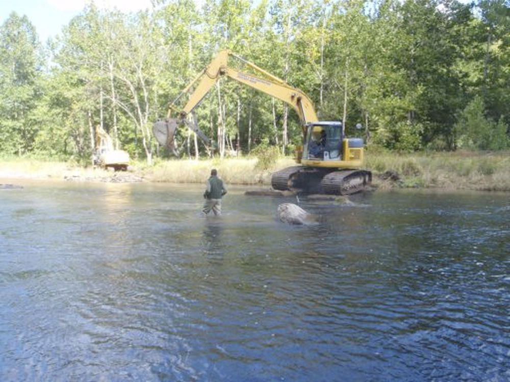 Escavators placing the boulders at 80 cfs.