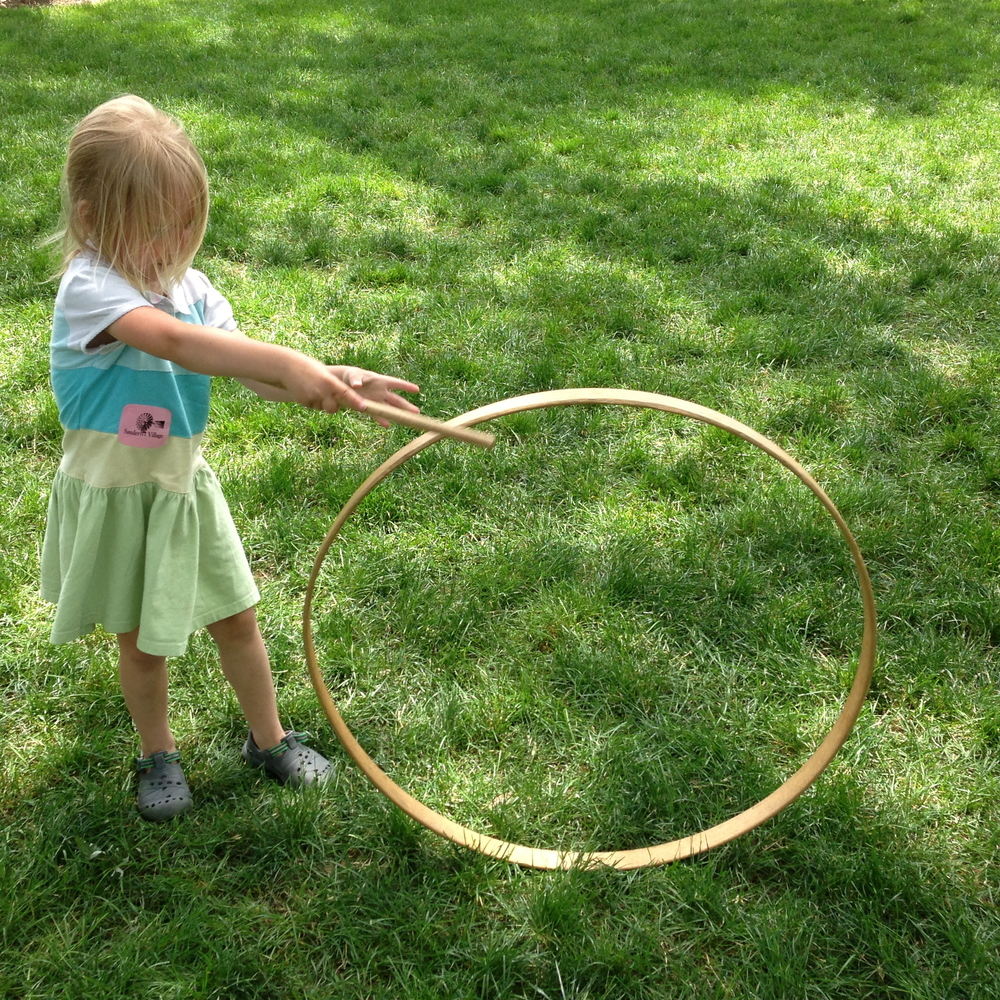 Cecilia playing with an old fashioned hula-hoop.