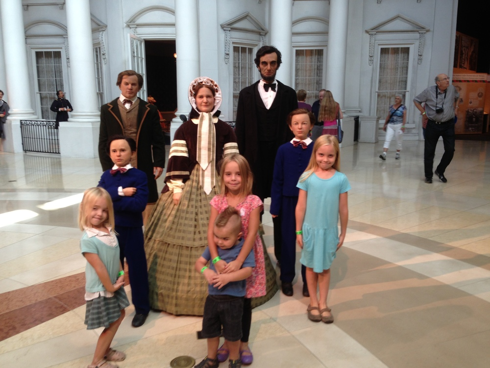 Standing next to very lifelike replicas of the Lincoln family.