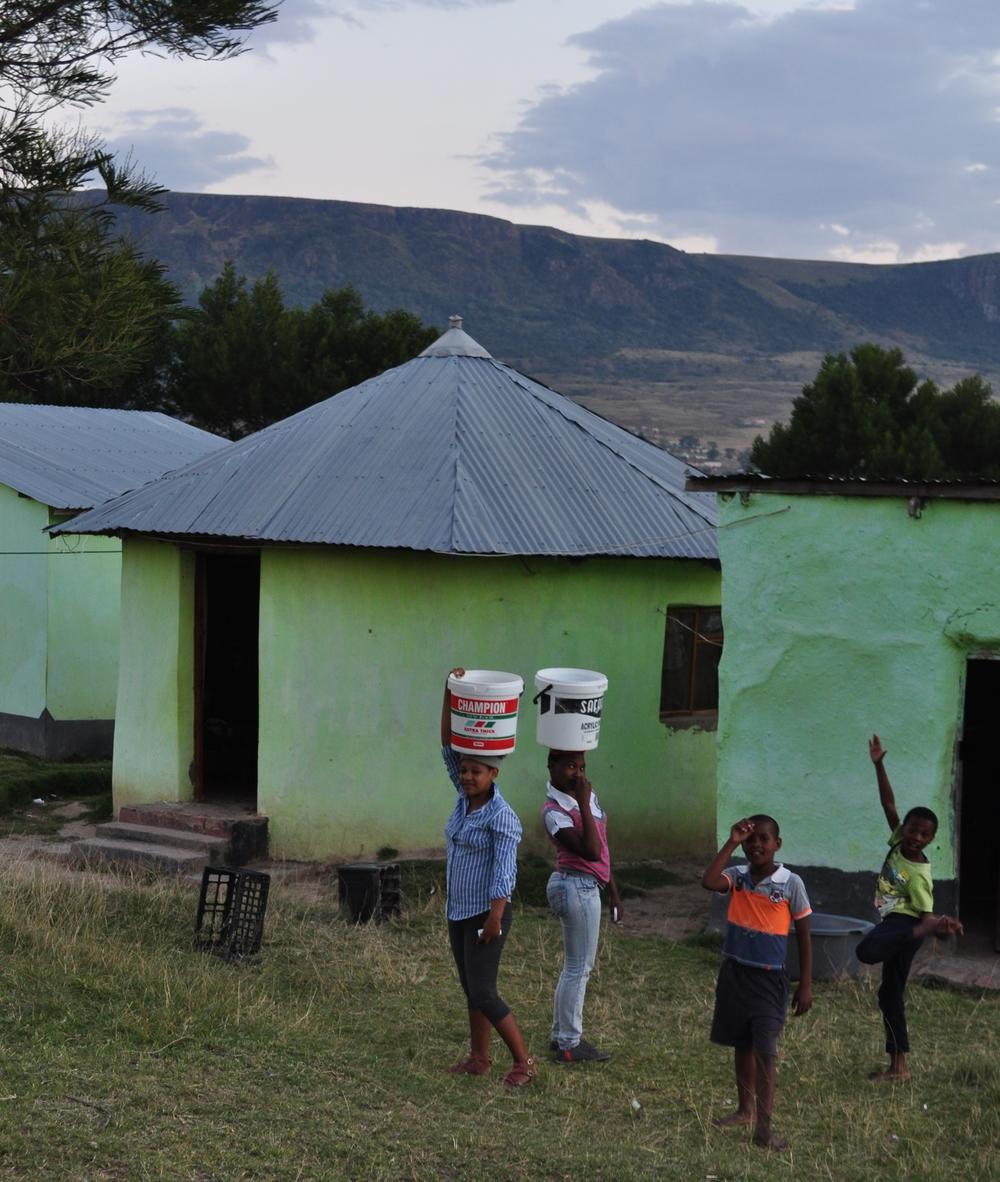 Pumla's neighbours balance buckets of water on their heads