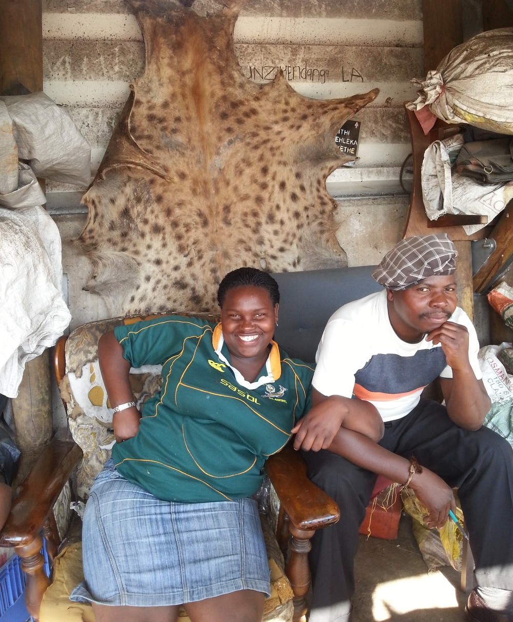 Two muthi traders sit under a hyena skin. How obvious is it that the brother was much less keen on being interviewed than the sister?