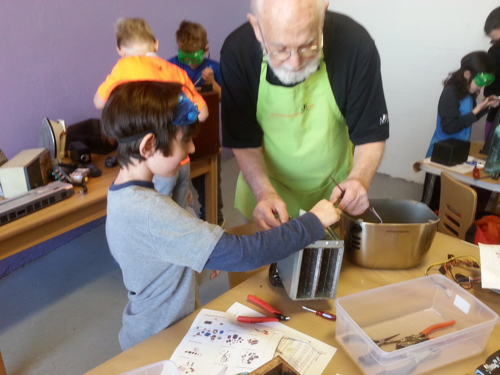 A Museum educator assists a young visitor in a Makerspace workshop