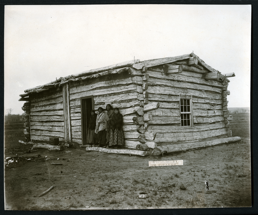 Two of Sitting Bull's wives and two of his daughters are pictured outside the cabin where he was killed.