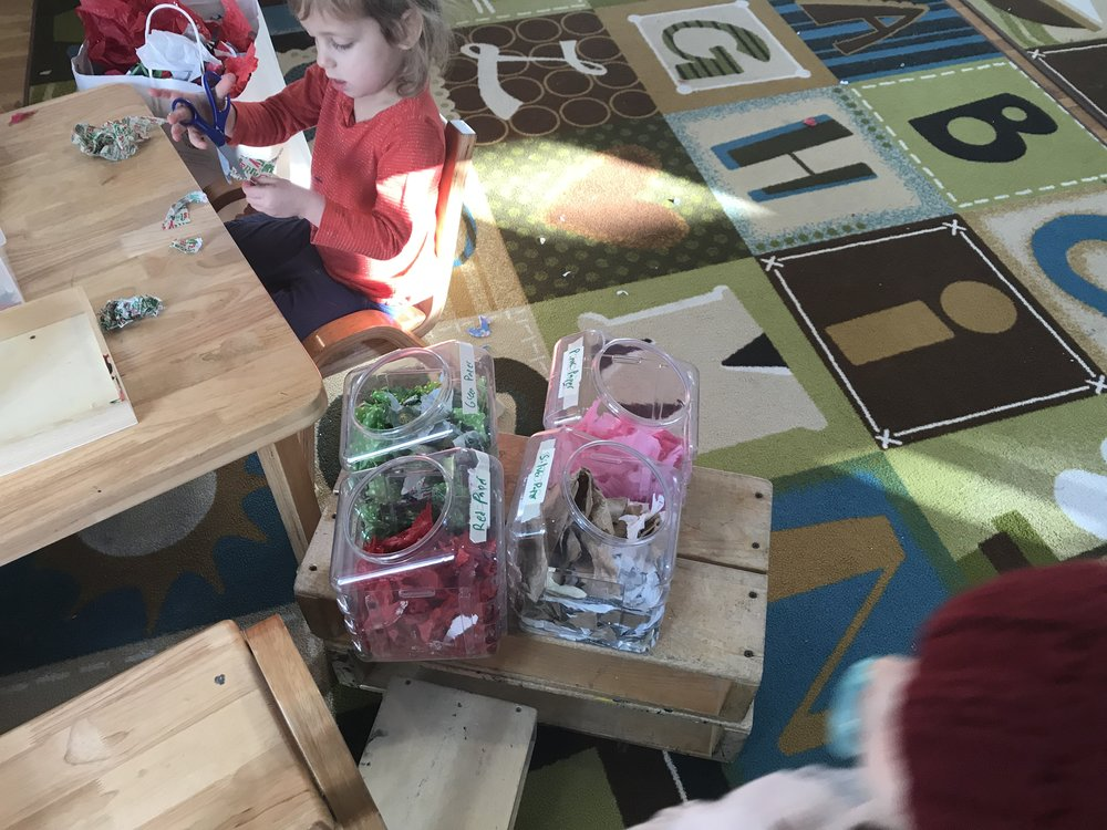 The children are sorting the scraps by color. This activity supports children's ability to sort by one attribute as well as literacy and reading as they sort the paper into labeled containers. The children will then be able to compare which color(s) have more or less.