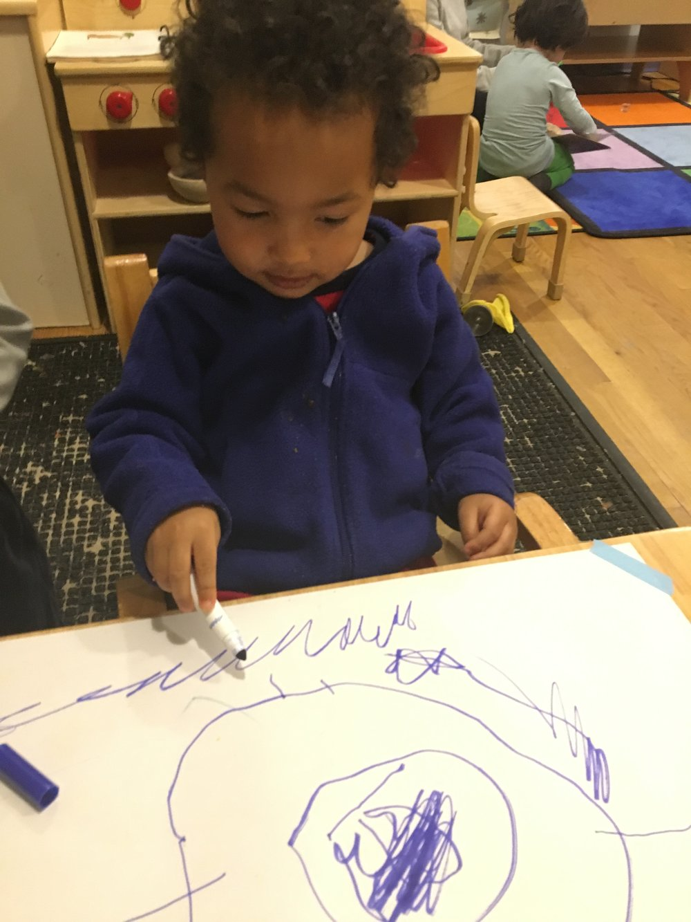 Drawing a picture of a person.  The circle is the body and then he added arms and legs.  He described his drawing as he drew. Learning Goals:  Representational Drawing, Fine Motor, Language