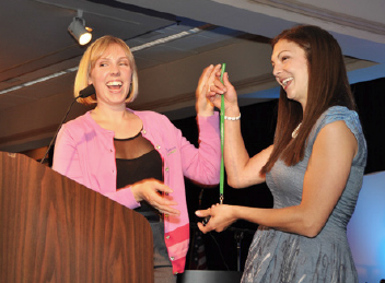 From one young to another, Lauren Reeves, the former Young & Free Maine Spokester, hands the coveted keys to the 'Green Machine,' the Young & Free Maine car, to the new Spokester, Mallory Lavoie, after Lavoie was introduced as the new Spokester at the League's Annual Awards Banquet.