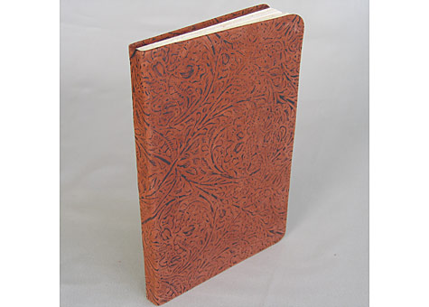 Binder: Lily Stevenson: Journal. The soft leather-bound blank book has handmade Iowa walnut fly leaves. The book block is Rives paper sewn on tapes. It is an experimental piece to see if embossed upholstery leather could be used to make a soft cover.