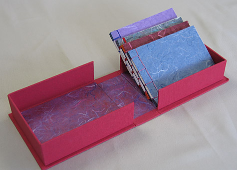 Binder: Lily Stevenson: Four Japanese Stab-bound Books in a Box. The red cloth-covered handmade box is lined with paper from Thailand. The set of four blank books is made from Thai mulberry paper.