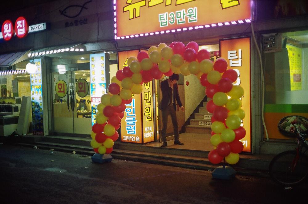 """A Dual-Tone Balloon Rainbow"" - And a bloke on the phone.  Seoul, Korea. Canonet QL17, Kodak 200 ColorPlus."
