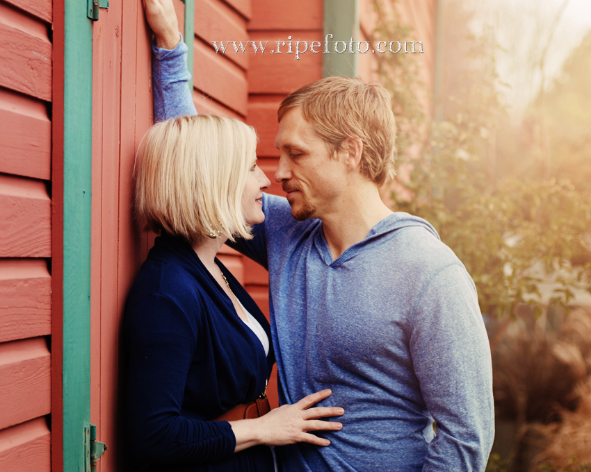 Portrait of couple against red barn by Portland photographer Ripe Photography.