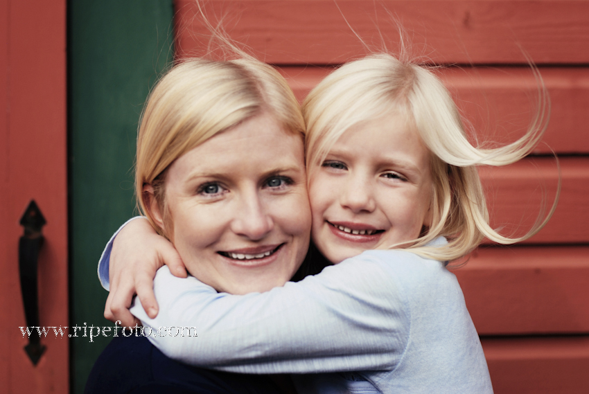 Portrait of mother and daughter against red barn by Portland photographer Ripe Photography.